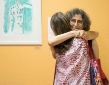 Artist, Chava, receives a celebratory hug from a friend